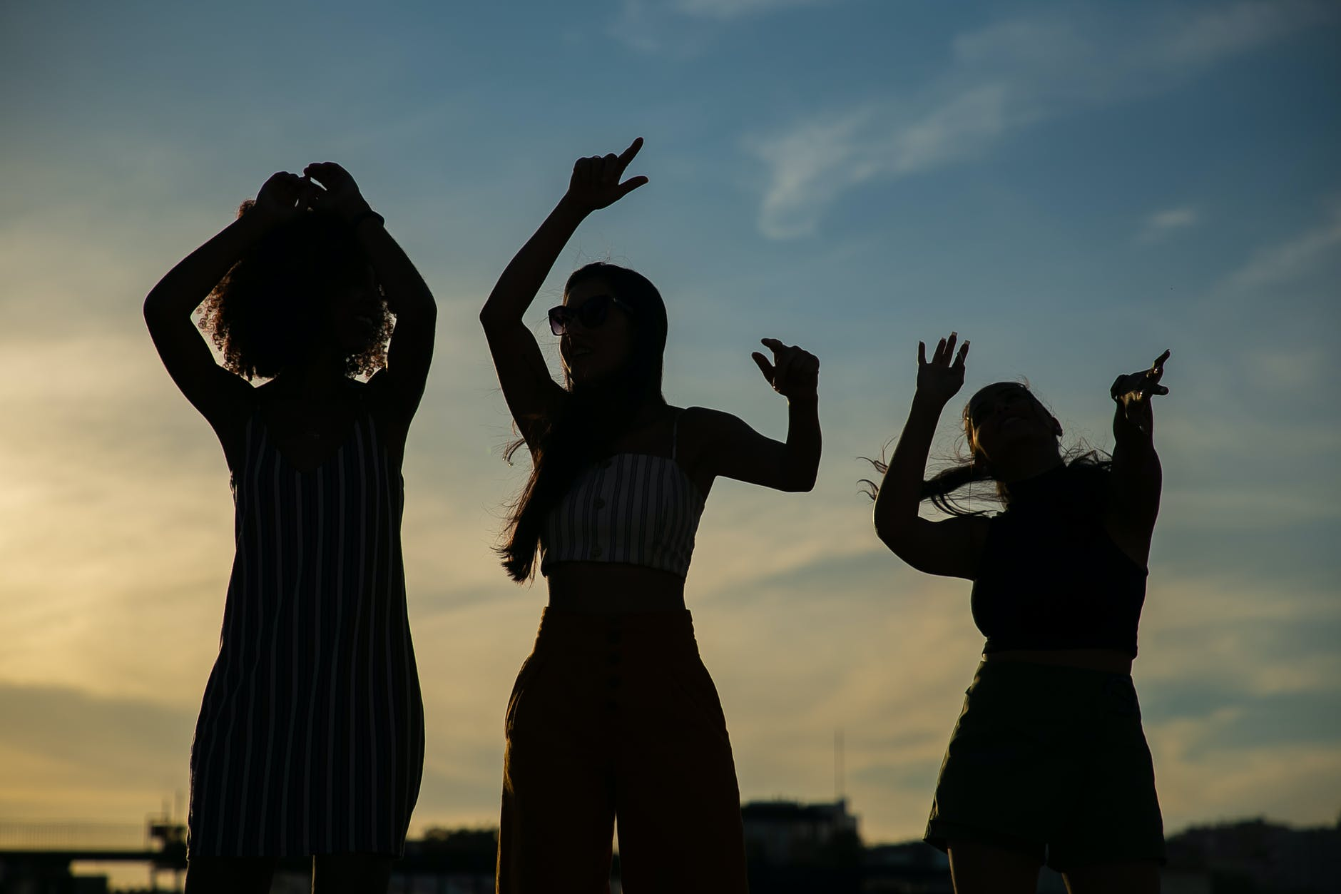 anonymous girlfriends dancing against sunset sky